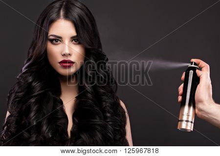 Beautiful brunette model with curls classic makeup and red lips with a bottle of hair products. The beauty of the face. Portrait shot in the studio on a gray background.
