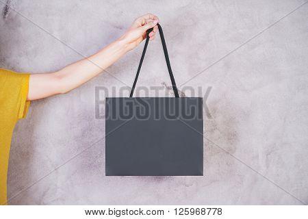 Female arm holding blank shopping bag on concrete background. Mock up