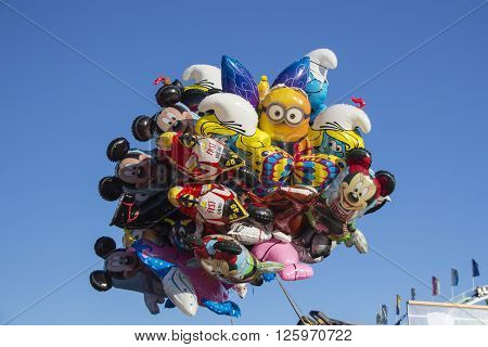 MUNICH, GERMANY - OCTOBER 02, 2015: Famous sculptures as balloons (Mickey Mouse Smurf) flying above the fairground of Oktoberfest