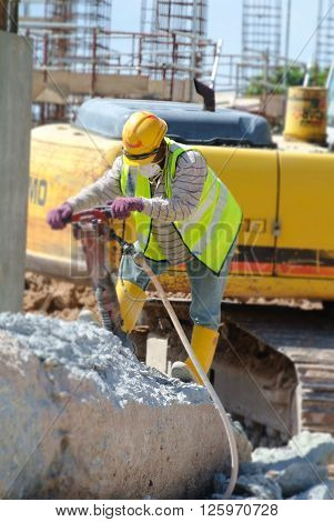 JOHOR, MALAYSIA -JANUARY 13, 2015: A construction workers cutting foundation pile using hacking method at the construction site. He using the heavy duty mobile hacker machine.
