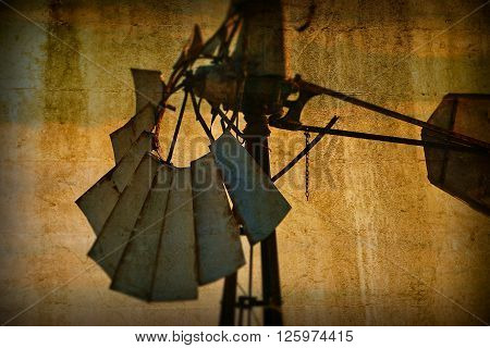 Background Vintage Australian Windmill on rural farming property pumping live stock bore from underground water table in salty, saline outback environment with plenty of history