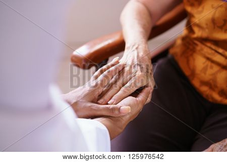 Old people in geriatric hospice: Black doctor visiting an aged patient holding hands of a senior woman. Concept of comfort and compassion