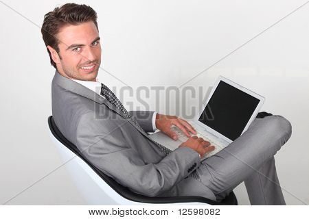 Smiling businessman in front of  a laptop computer