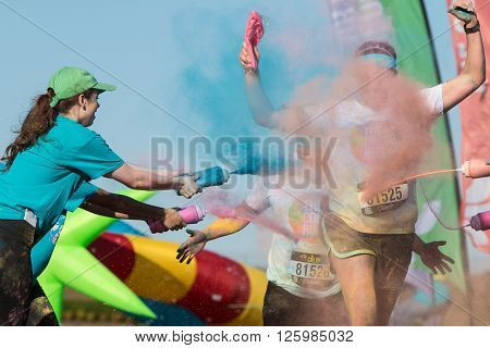 HAMPTON, GA - APRIL 2016: Volunteers douse runners with colored corn starch at The Color Run in Hampton GA on April 2 2016 .