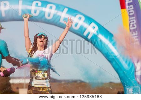 HAMPTON, GA - APRIL 2016: A woman extends her arms in jubilation as she's doused with colored corn starch at The Color Run in Hampton GA on April 2 2016 .