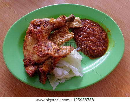 'Ayam Penyet' meal on street table setup. Ayam penyet is Indonesian cuisine. fried chicken dish consisting of fried chicken served with sambal slices of cucumbers tempe and rice.