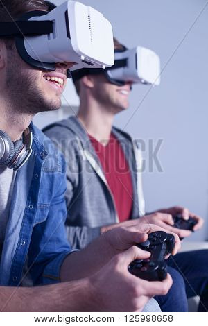 What a cool game. Cheerful two men are competing in play station. They are sitting on sofa with a virtual reality headset. The friends are smiling