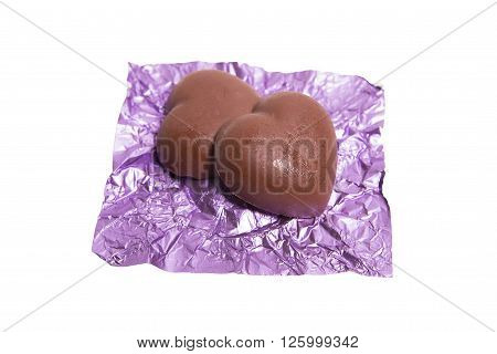 Two chocolate heart candy in puple foil on white background