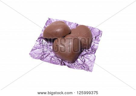 Three chocolate heart candy in puple foil on white background, chocolate candy concept , chocolate candy idea, chocolate candy background, chocolate candy isolated, chocolate candy valentine.