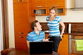 Man watching something on laptop, his wife is angry poster