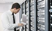 young it engeneer business man with thin modern aluminium laptop in network server room poster