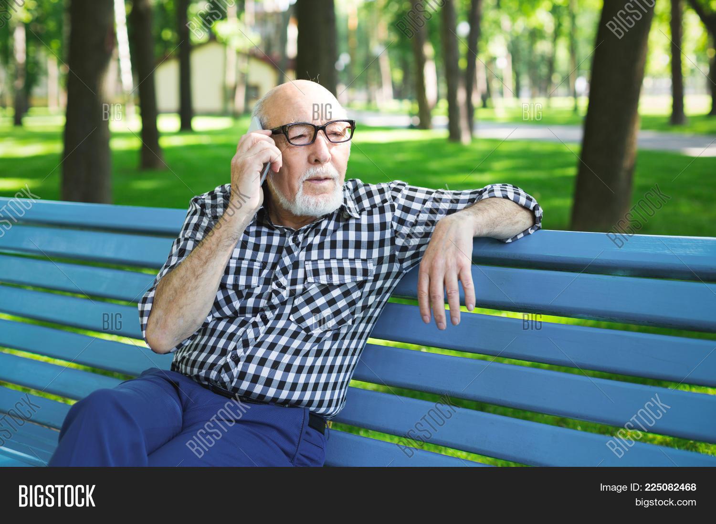 1f7ae46f4d852 Worried senior man with smartphone outdoors. Elderly casual man in  eyeglasses having emotional conversation on