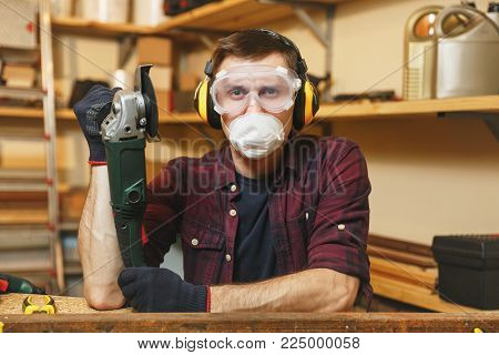 Caucasian young man in plaid shirt, black T-shirt, noise insulated headphones, protective mask working in carpentry workshop at wooden table place with different tools, sawing iron with power saw