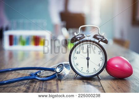 Healthy checking plan concept. Alarm clock with medical instruments stethoscope and red heart on wood table and blurred science lab accessories background.