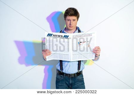 Portrait of assertive man looking through newspaper. Painted reflection reflecting on wall. Press concept
