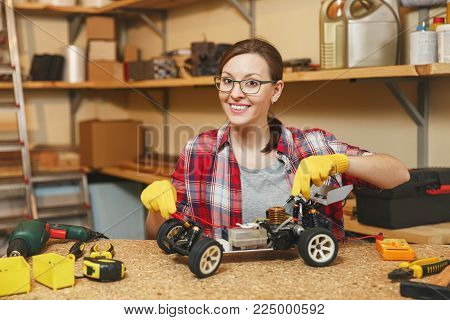 Young woman in plaid shirt, gray T-shirt, yellow gloves making toy car iron model constructor, working in carpentry workshop at wooden table place with different tools. Multimeter for electrician poster