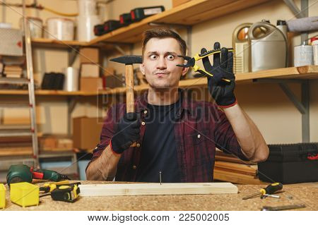 Crazy fun mad caucasian young man in plaid shirt, black T-shirt, gloves hammering nails with hammer, working in carpentry workshop at wooden table place with piece of wood, pliers, different tools