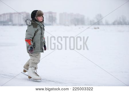 Ice skating boy on the lake.The boy is skating on the lake. Little baby in huge skates