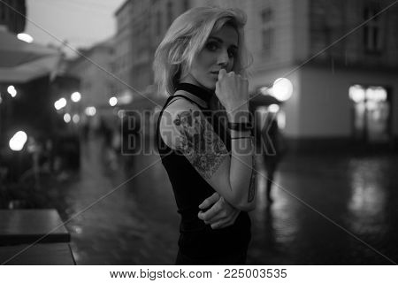 Young woman with tattoo on shoulder stands on city street in evening in rain. In background there are city lights and people passing by. Black&white image.