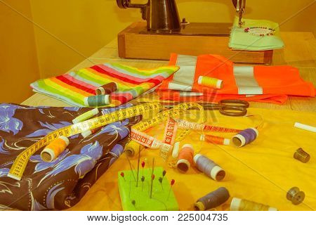 Sewing still life: colorful cloth. scissors and sewing kit includes threads of different colors, thimble and other sewing accessories on wooden table. tools for sewing for hobby