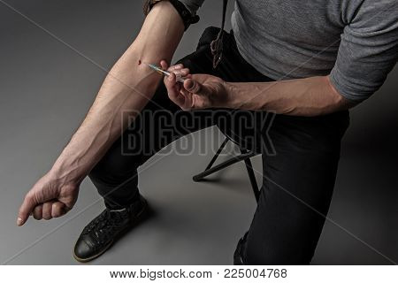 Top view of narcomaniac inserting dope through a needle while sitting on chair