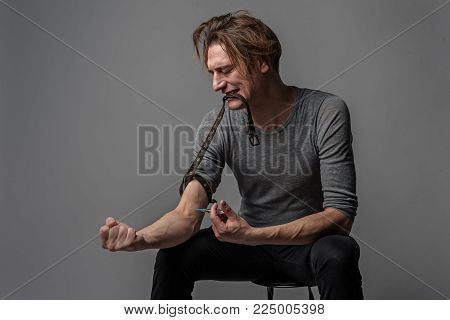 Disheveled narcomaniac man sitting on chair and injecting a drug into a vain with eager. Isolated on background