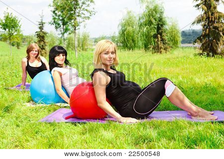 Three pregnant  women relaxing on grass