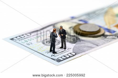 Businessmen miniature figurine macro photo. Cash money - USA banknote and coin. Business agreement profit. Successful business strategy. Market share growth by merge and acquisitions. Company budget