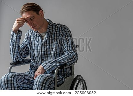 Portrait of depressed young man in chair with wheels unable moving by himself. Copy space in right side. Isolated on background