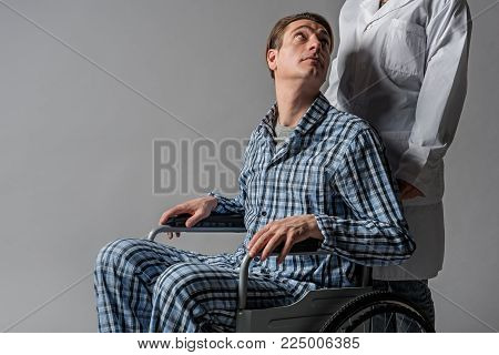 Calm male invalid sitting in wheelchair and looking at his doctor with hope. Isolated on background