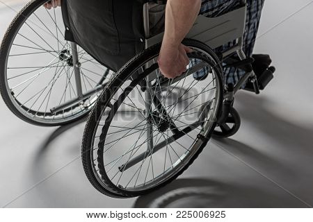 Close up of male hands using invalid carriage. Sickness concept