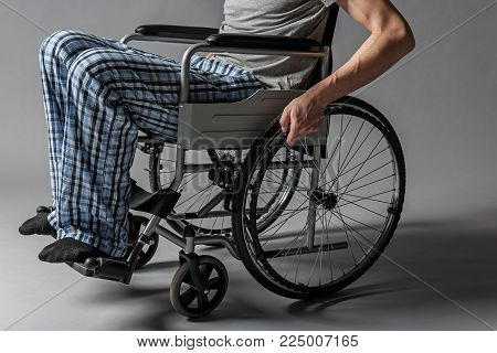 Close up of paralyzed lower half of the man body confined to a wheelchair. Illness concept