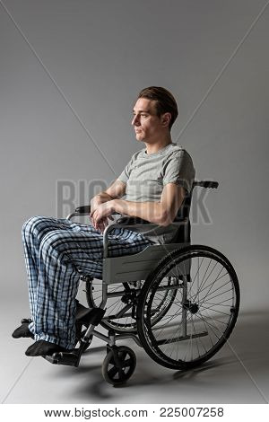 Ruined life concept. Side view of depressed male person disabled sitting in wheelchair