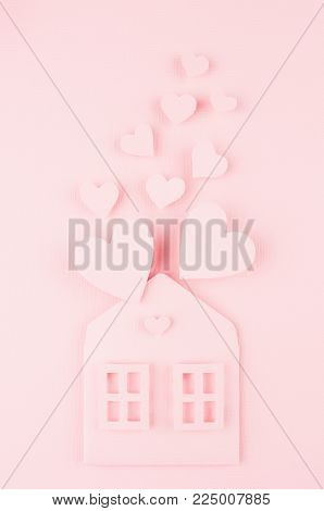 Paper house with fly out red hearts on soft pink color background. Valentine day concept for design.