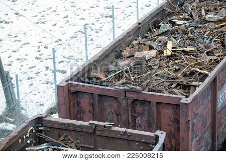 Railway wagon in winter filled with metal scrap. Old rusty corroded metal, abstract for ecology.