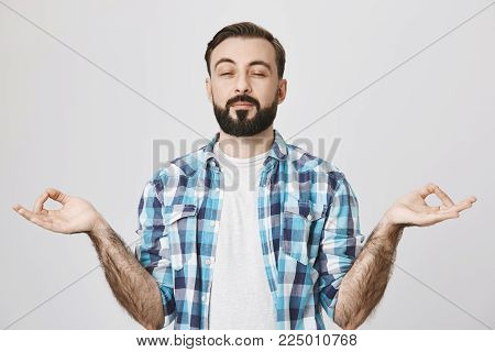 Indoor shot of funny bearded man trying to meditate, showing zen gesture, squinting because he unfocused, standing against gray background. Wife suggested yoga to relax but he do not take it serious.