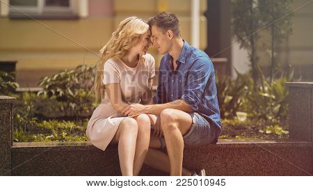 Couple sitting on bench holding hands and nuzzling, sweet tender relationship, stock video