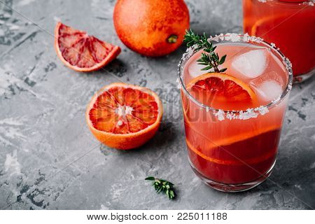 Blood Orange Sangria with ice and thyme on dark backgorund