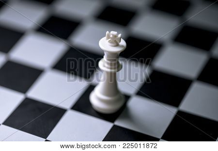 White king on chess board. Chess game figure on checkered board. White king alone on chessboard. Mate situation in chess rules. Business advantage or strong leadership concept. Chess king closeup