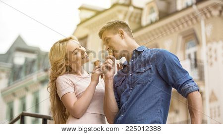 Playful young couple eating ice cream and flirting, sweet date in summer, stock video