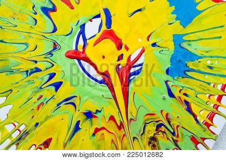 artistic work, drawing, background concept. close up of huge splash creating with gouache paints of various colores, yellow is the main here and there is also red, blue, green
