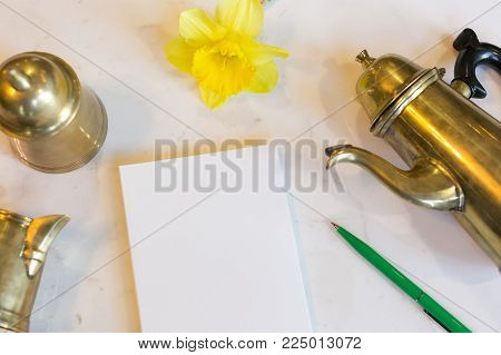 drawing, tea ceremony, rest concept. on the marble table there is vintage bronze teapot and small bell made of the same material, they are placed by scrapbook and pen