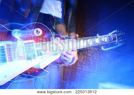 performance, creativity, rock style concept. close up of guitar in the arms of caucasian male musician, that figure is getting lost and blurred on the dark background