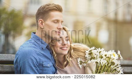 Man in love hugging beloved girlfriend, happy young lady holding nice flowers, stock video