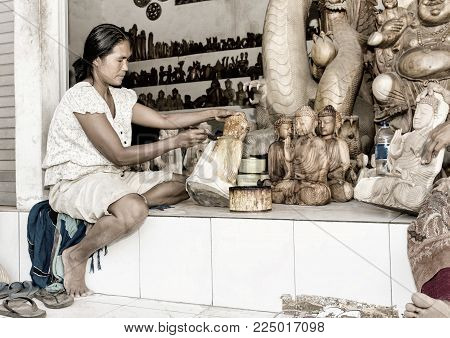 A woman is saturating with stain wooden Buddha. Bali. Ubud. Indonesia