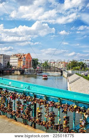 Wroclaw/Poland- August 18, 2017: Wroclaw cityscape with river Odra from Tumski bridge - touristic boat, historical and modern  houses, walking people, green trees and blue sky