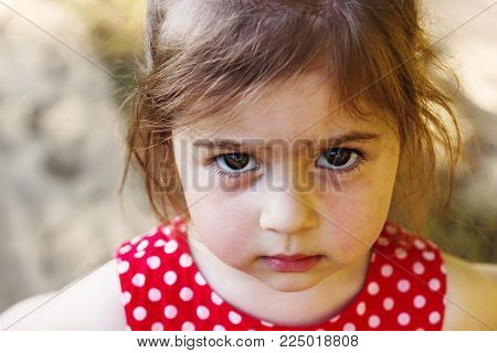 Portrait of cute sad little girl looking at camera at summer day