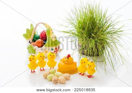 Yellow Easter Chicks and basket ceramic Easter eggs on a light background. Copy space. Easter composition.