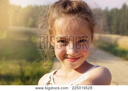 Happy cute girl making selfie over sunny park. Cute preteen Girl smiling very happy, surprised on Summer background. Looking at camera.