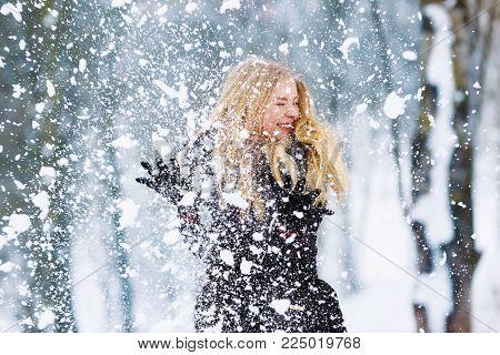 Winter young woman portrait. Beauty Joyful Model Girl laughing and having fun in winter park. Beautiful young woman laughing outdoors. Enjoying nature, wintertime.
